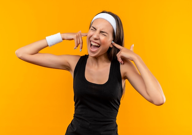 Angry young pretty sporty girl wearing headband and wristband putting fingers in ears with closed eyes isolated on orange wall