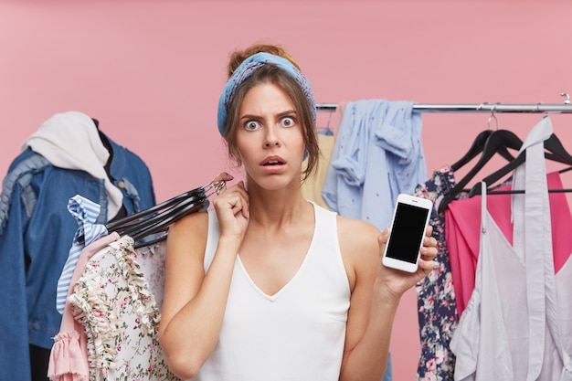 Angry young pretty woman looking with dissatisfaction, keeping hangers with clothes on shoulder, holding smart phone in hand with blank screen