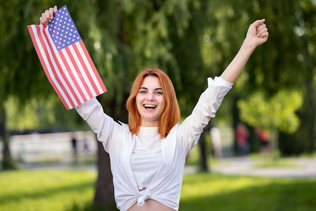 Angry young red haired woman protester posing with usa national flag in her hand standing outdoors in summer park.