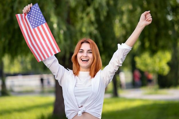 Сердитый молодой красный с волосами протестующий женщины представляя с национальным флагом сша в ее руке стоя outdoors в парке лета.