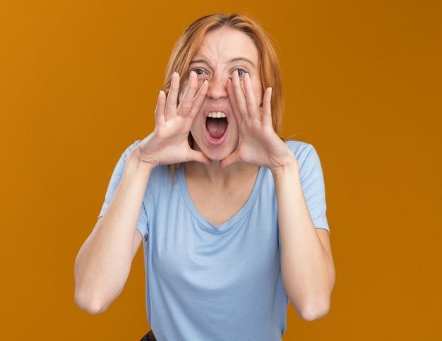オレンジ色の顔の近くで手をつないでそばかすと怒っている若い赤毛生姜の女の子