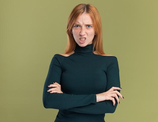 そばかすがオリーブグリーンに腕を組んで立っている怒っている若い赤毛生姜の女の子