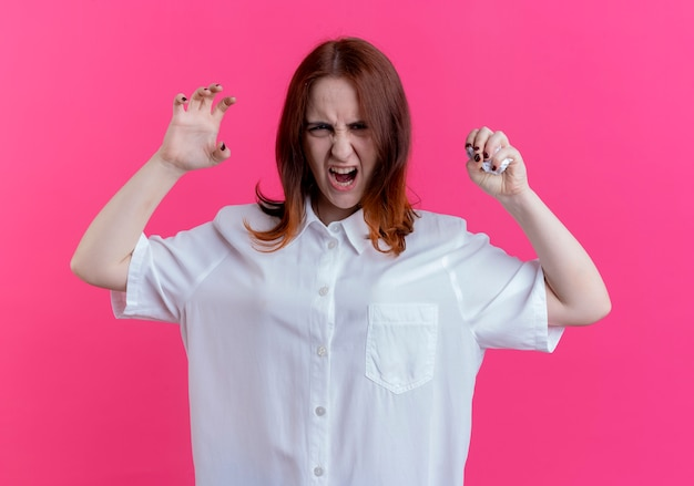Angry young redhead girl crushing paper and doing tiger style isolated on pink wall