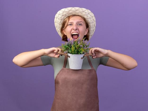 コピースペースと紫色の壁に分離された植木鉢に花を保持しているガーデニング帽子をかぶって怒っている若いスラブ女性庭師