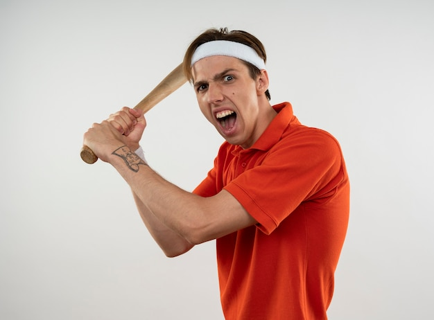 Angry young sporty guy wearing headband with wristband holding baseball bat isolated on white wall