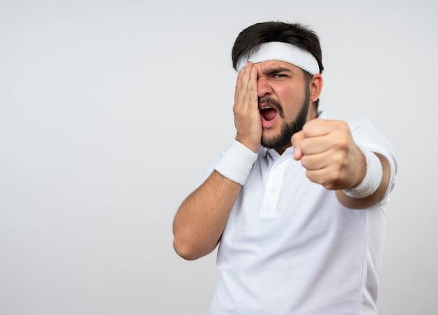 Сердитый молодой спортивный человек с повязкой на голову и браслетом, протягивающим кулак, положив руку на лицо, изолированное на белой стене с копией пространства