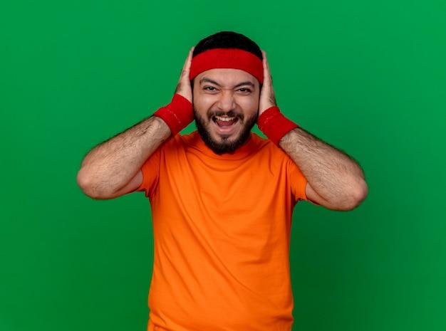 Arrabbiato giovane uomo sportivo che indossa la fascia e il braccialetto mettendo le mani sulle orecchie isolate su priorità bassa verde