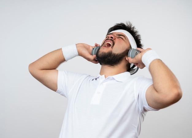 Arrabbiato giovane sportivo con gli occhi chiusi che indossa la fascia e il braccialetto con le cuffie isolate su bianco