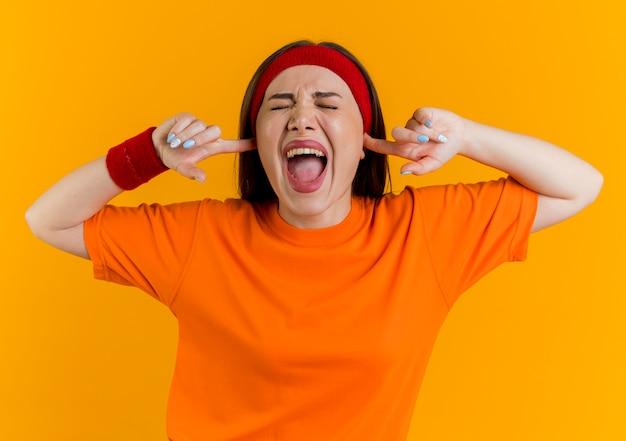 Arrabbiato giovane donna sportiva che indossa la fascia e braccialetti mantenendo le mani nelle orecchie urlando con gli occhi chiusi