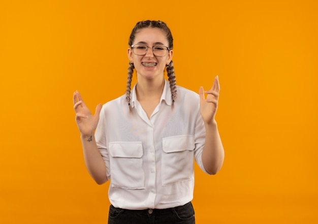 オレンジ色の背景の上に立って腕を上げて叫んで欲求不満のカメラを見て白いシャツのおさげのメガネで怒っている若い学生の女の子