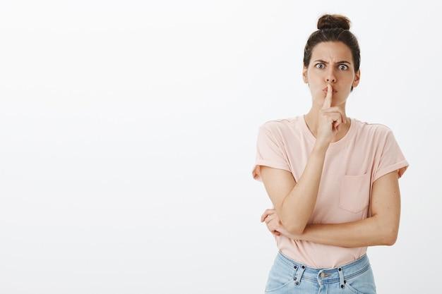 Giovane donna alla moda arrabbiata che posa contro il muro bianco