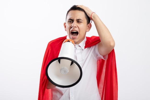 コピースペースと白い背景で隔離のラウドスピーカーで叫んでいる側を見て頭に手を置いて赤い岬の怒っている若いスーパーヒーローの少年