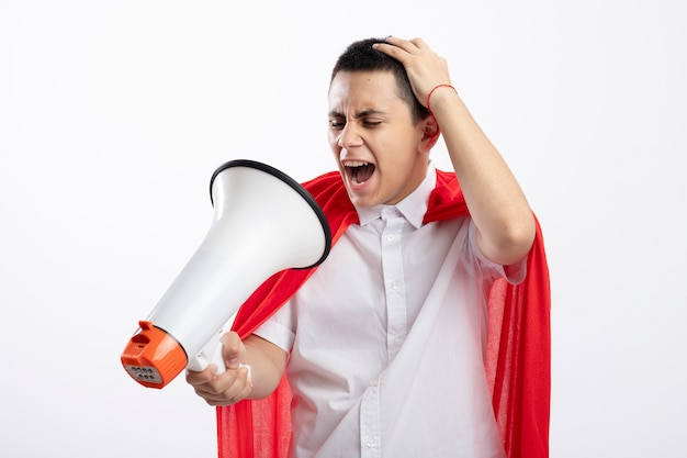 Angry young superhero boy in red cape holding and looking at speaker putting hand on head screaming isolated on white background