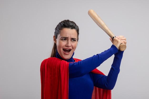 Angry young superhero girl raising baseball bat isolated on white background