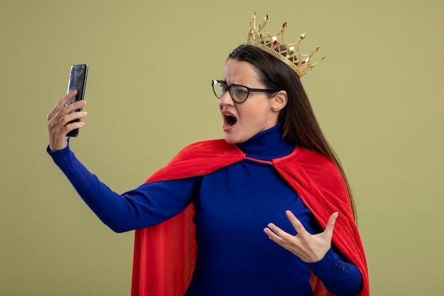 眼鏡と王冠を身に着けて、オリーブグリーンで隔離の電話を保持し、見て怒っている若いスーパーヒーローの女の子