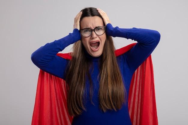 眼鏡をかけている怒っている若いスーパーヒーローの女の子は、白で隔離の頭をつかんだ
