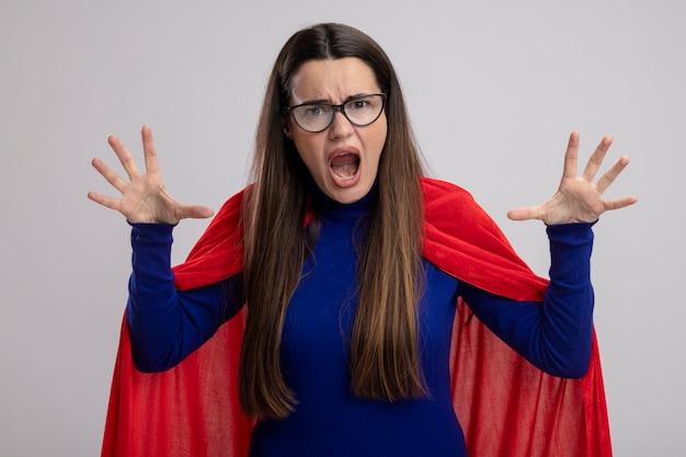 白で隔離の手を上げる眼鏡をかけている怒っている若いスーパーヒーローの女の子