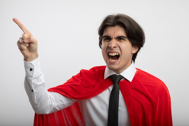 Angry young superhero guy looking at side wearing tie points at side isolated on white background
