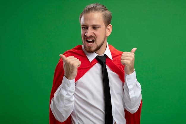 엄지 손가락에 고립 된 녹색을 보여주는 성 난 젊은 슈퍼 히어로 남자