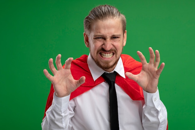 Angry young superhero guy showing tiger style gesture isolated on green