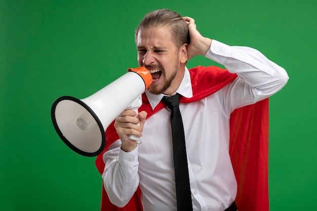Сердитый молодой супергерой говорит по громкоговорителю и кладет руку за голову, изолированную на зеленом