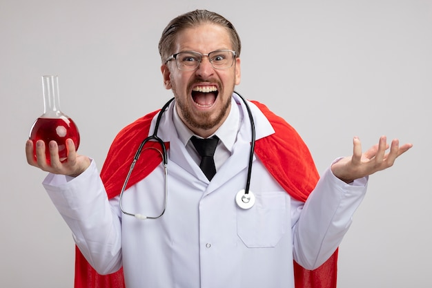 Angry young superhero guy wearing medical robe with stethoscope and glasses holding chemistry glass bottle filled with red liquid isolated on white background