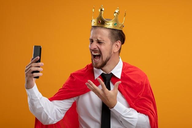 넥타이와 왕관을 착용하고 오렌지에 고립 된 전화를보고 화가 젊은 슈퍼 히어로 남자