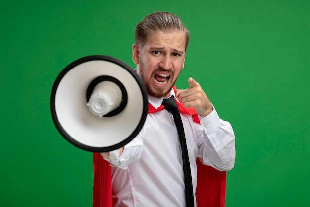 Angry young superhero guy wearing tie holding out loudspeaker at camera and showing you gesture isolated on green background