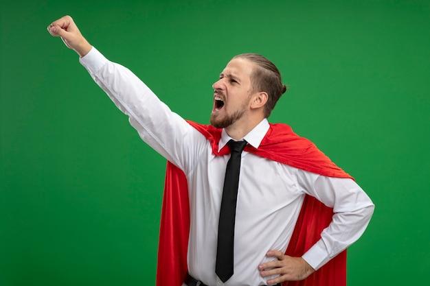 Сердитый молодой супергерой в галстуке смотрит на бок, поднимающий кулак, изолированный на зеленом фоне