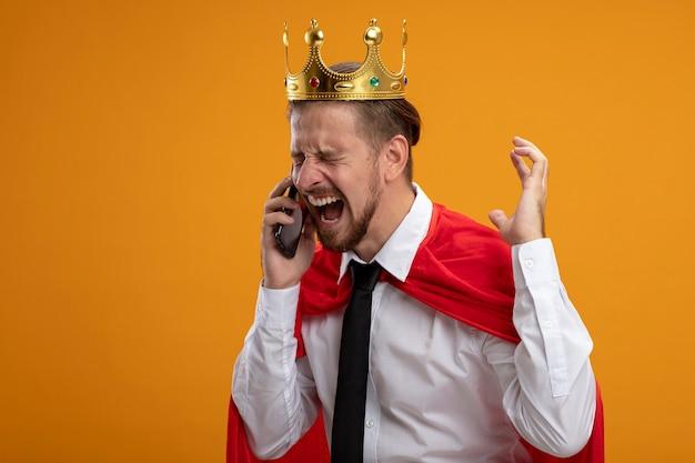 ネクタイと王冠を身に着けている目を閉じて怒っている若いスーパーヒーローの男は、オレンジ色の背景で隔離の電話で話します