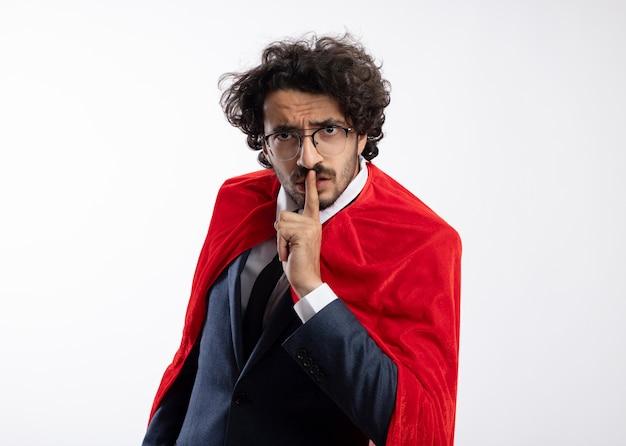 白い壁に分離された赤いマントのジェスチャーの沈黙のサインとスーツを着て光学メガネで怒っている若いスーパーヒーローの男
