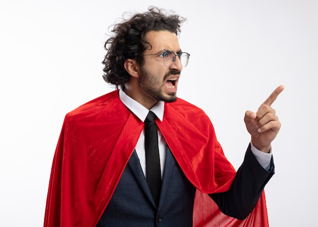 Angry young superhero man in optical glasses wearing suit with red cloak looks and points at side isolated on white wall