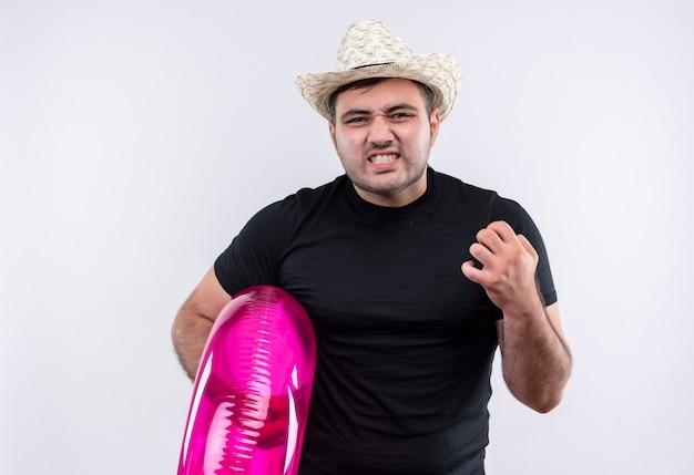 Uomo arrabbiato giovane viaggiatore in maglietta nera e cappello estivo che tiene anello gonfiabile con espressione infastidita in piedi sopra il muro bianco