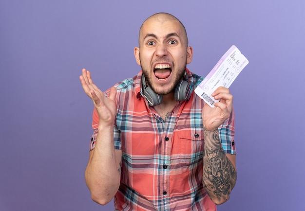 Arrabbiato giovane viaggiatore con le cuffie intorno al collo tenendo il biglietto aereo isolato sulla parete viola con spazio di copia
