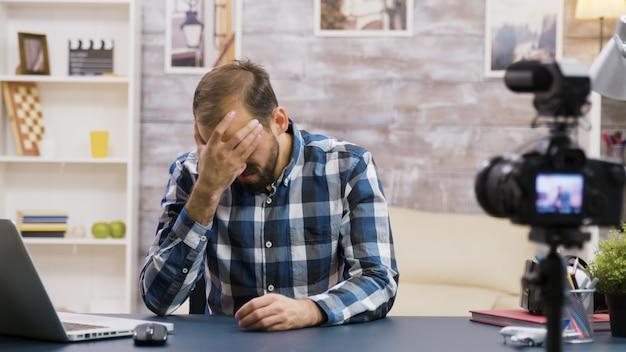 Giovane vlogger arrabbiato mentre registra un nuovo podcast per il suo pubblico sui social media. famoso influencer.
