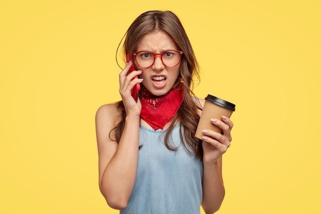 La giovane donna arrabbiata si sente intensa mentre ha una conversazione telefonica con un amico, sente sciocchezze, non è d'accordo con qualcosa, sorride con disapprovazione, beve caffè, isolato su un muro giallo.