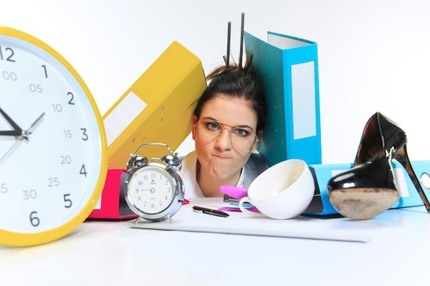 Сердитый. молодая женщина получает много работы и сроки, находясь под давлением сделок. нажал папками с бумагами. понятие проблем офисного работника, бизнеса, проблем и стресса.