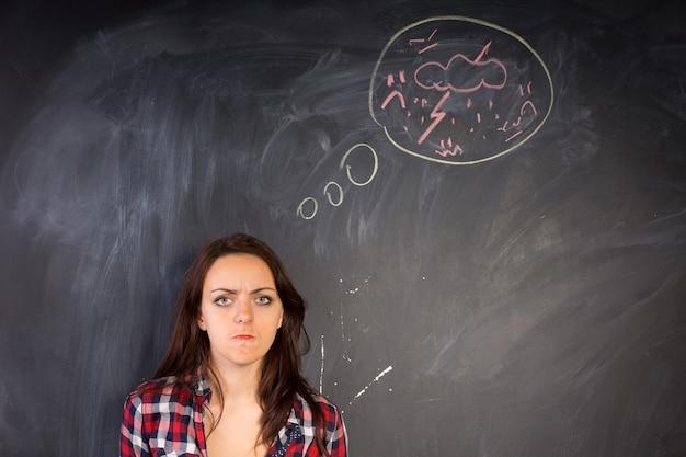 Сердитая молодая женщина смотрит в камеру, изображая ярость, как показано на нарисованной от руки схеме молнии и грома на доске рядом с ней.