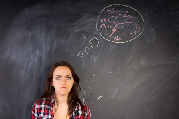 Angry young woman glaring at the camera in a depiction of rage as shown by the hand-drawn diagram of a bolt of lightning and thunder on the chalkboard alongside her