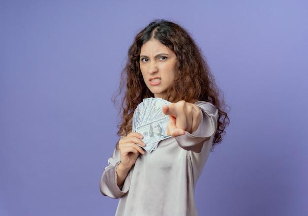 現金を保持し、青で隔離のジェスチャーを表示している怒っている若い女性