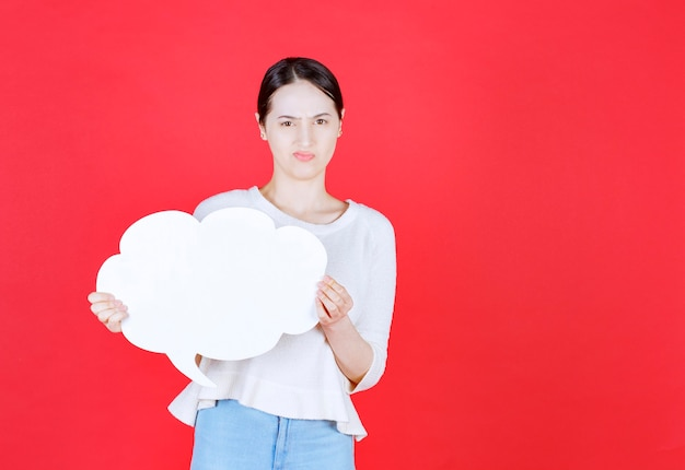 Angry young woman holding speech bubble with a cloud shape