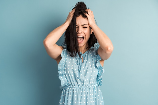 美しい水玉模様のドレスを着た怒っている若い女性が青い壁に怒って叫ぶ