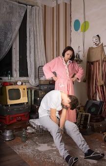 ジャンクルームでケージに座っている彼女の眠っているパートナーを見ているピンクのローブの怒っている若い女性。