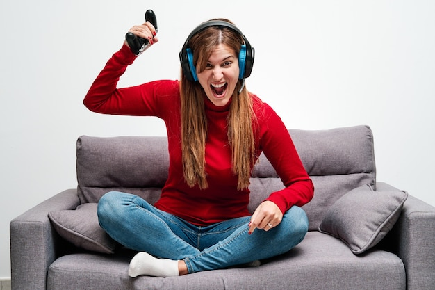 Angry young woman playing video games at home