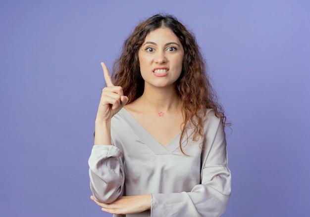 怒っている若い女性は、コピースペースで青に分離された側を指しています