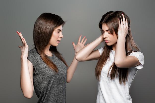 Сердитая молодая женщина кричит на того, кто закрывает ей руки. ссора между двумя сестрами