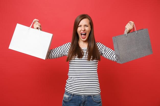 화난 젊은 여성은 밝은 붉은 벽 배경에서 격리된 쇼핑 후 구매한 패키지 가방을 들고 손을 벌리고 비명을 지릅니다. 사람들은 진심 어린 감정, 라이프 스타일 개념입니다. 복사 공간을 비웃습니다.