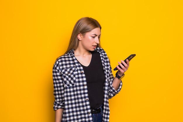 휴대 전화와 함께 성 난 젊은 여자. 노란색 벽에 휴대 전화를 가진 여자의 초상화