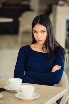 カフェで組んだ腕を持つ怒っている若い女性