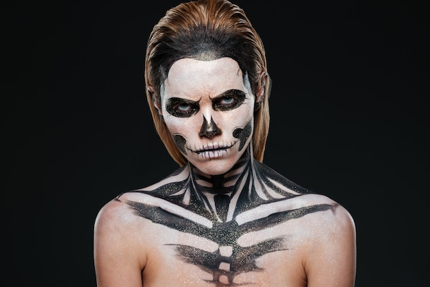 Angry young woman with gothic halloween makeup over black background